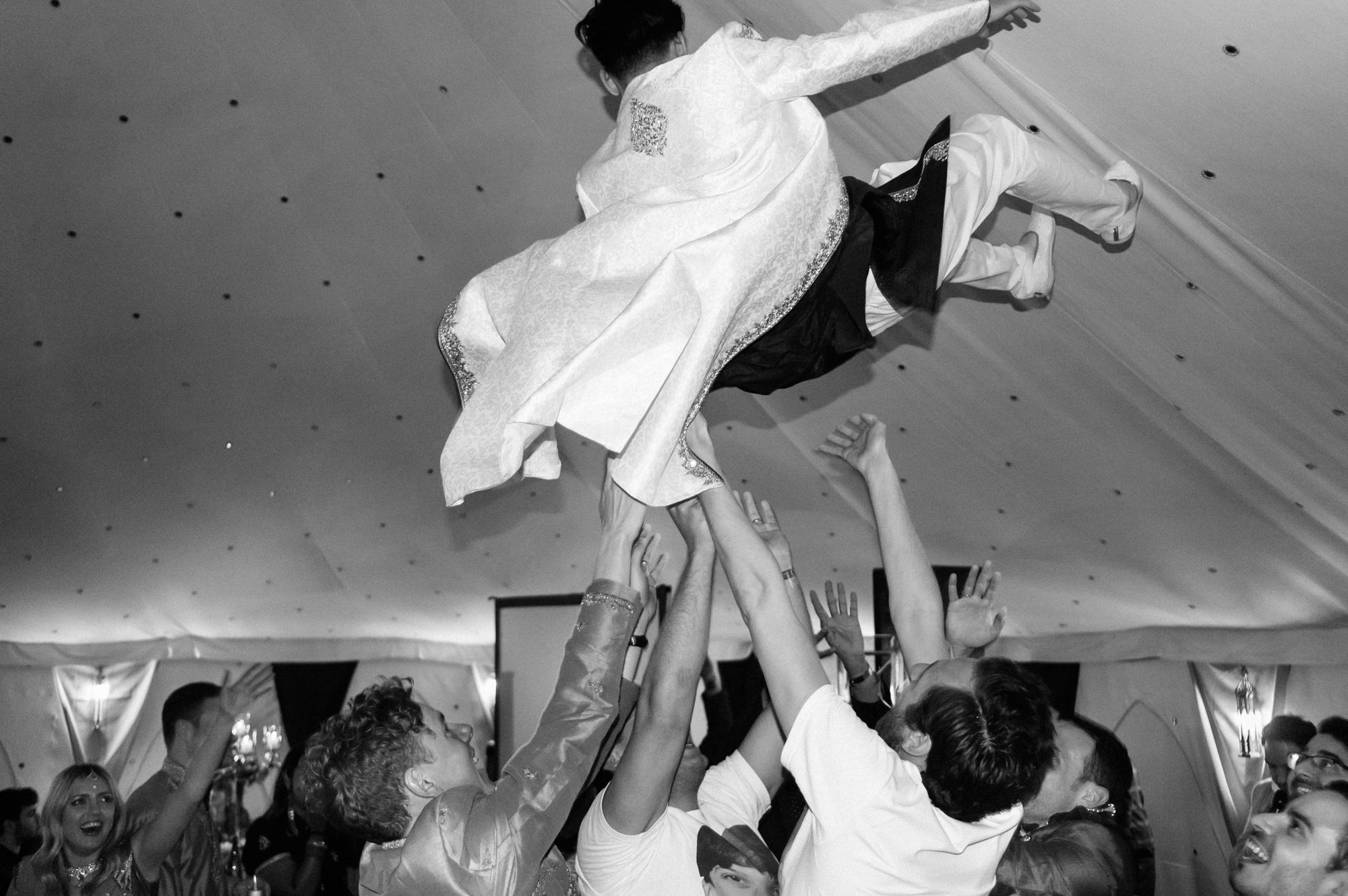 groom thrown in air indian wedding solihull